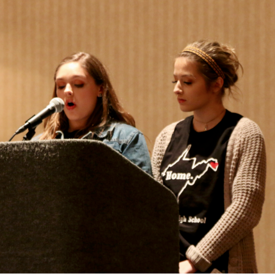 Young women reading their writing at a conference